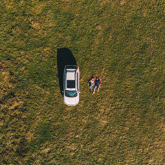 overhead aerial view car at green grass field couple laying on blanket
