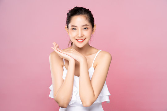 Beautiful Young Asian woman with clean fresh white skin touching her own face softly in beauty pose. Girl put hands under chin in pink background. Facial treatment, cosmetology, spa, make up concept.