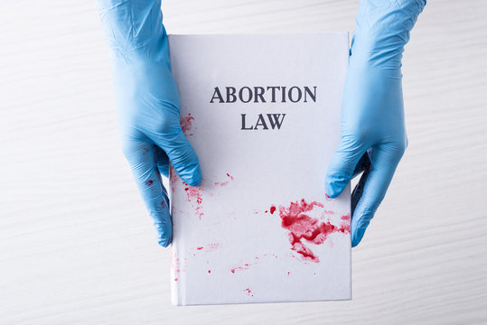 cropped view of doctor in latex gloves holding book with abortion law letters