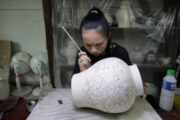 Painter works on a liquor vessel at a ceramic plant of Jindiao company in Jingdezhen