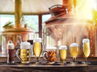 Wall Mural - Beer glasses on wooden table and copper brewing cask at the background.