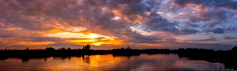 Panorama Reflection of vivid sunset sky reflection in  water.Colorful sunrise with Clouds over Lake at Koh Klang nam , Sisaket province,Thailand,ASIA.