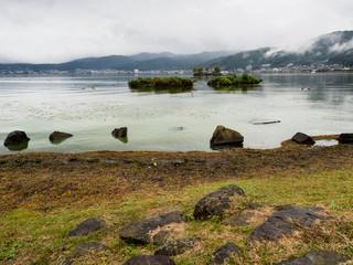 Rainy day on Lake Suwako with heavy clouds covering the surrounding mountains - Kamisuwa, Nagano prefecture, Japan
