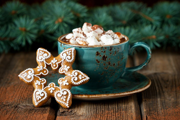 Ceramic mug filled with hot chocolate and gingerbread cookies
