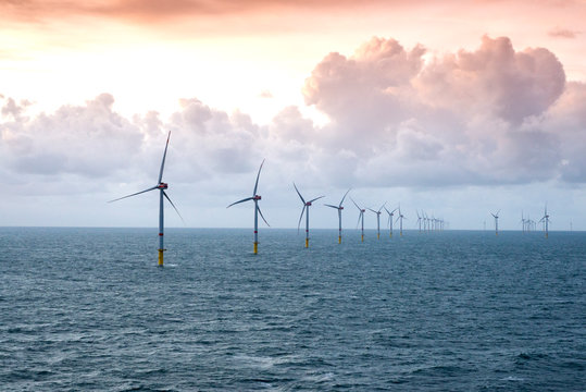 Sunset over offshore wind farm - green power generation
