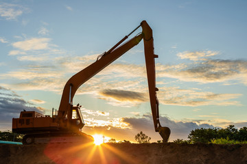 Silhouette of big tracked excavator digging the soil on site