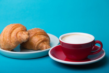 red cup with croissant on a blue background