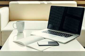 Open laptop on table near sofa, home interior. Freelancer workplace concept
