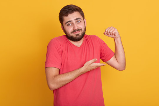 Horizontal shot of male in sleeveless t shirt show his weak biceps muscles, close up portrait of young handsome unshaven man posing isolated over yellow wall background, attractive guy with beard.