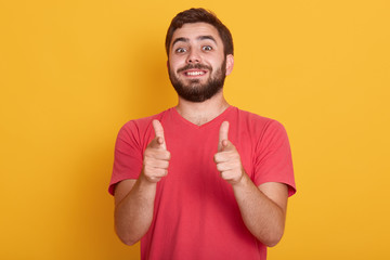 Picture of handsome smiling modern man dresses red casual t shirt showing ok sign with both thumbs, model posing isolated over yellow background, bearded young male with happy facial expression.