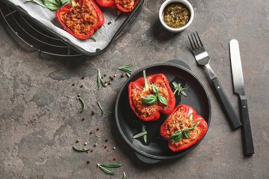 Tasty stuffed pepper with sauce on grunge background