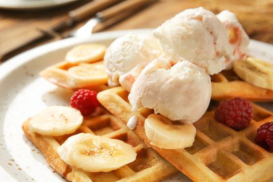 Tasty waffles with banana and ice-cream on plate, closeup