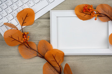 blank picture frame and white keyboard on wooden table for work place design, decorated with orange berries. top view.