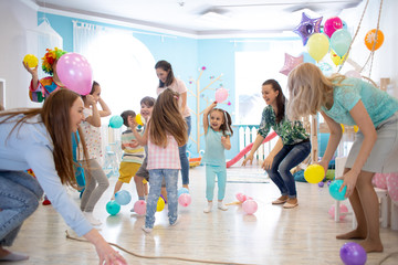 Jolly little kids and parents playing together on birthday party in children centre or club