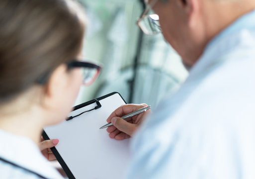 Doctor and nurse write on paper, discuss patient's diet
