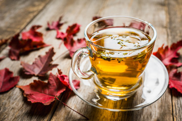Hot tea in glass cup with atmospheric autumn decorations. Selective focus. Shallow depth of field.
