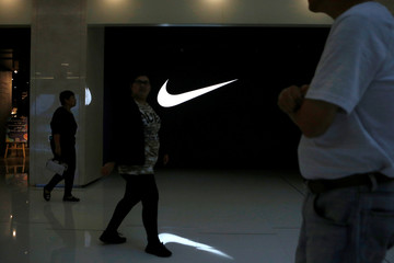 People walk past a Nike logo outside its store at a shopping mall in Beijing