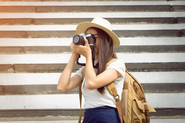 Fototapeta Young Asian woman photographer taking photo camera travel vacation with backpack - Vintage Tones  P obraz