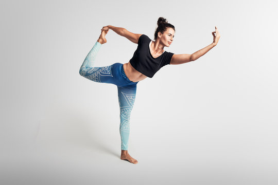 Yoga dancer pose, balance pose,  stretching, hands above head, woman on white backgroung, studio photos