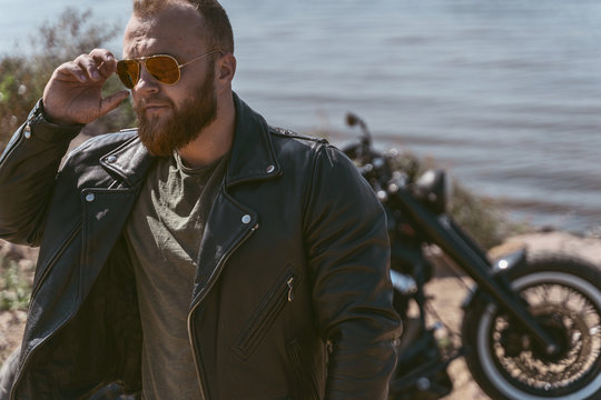Portrait of a cool biker fixing his sunglasses posing next to his bike