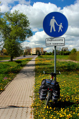 """Bike on a pedestrian footpath. Sign in Polish reads """"Bicycle traffic allowed""""."""