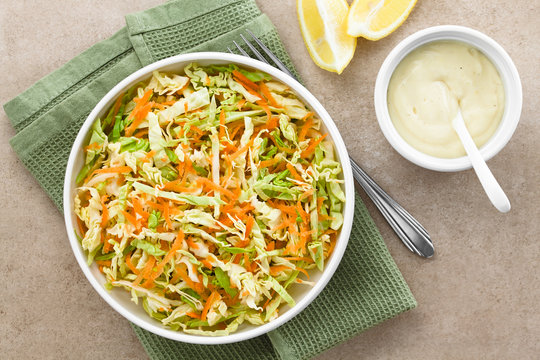 Coleslaw made of freshly shredded white cabbage and grated carrot with homemade mayonnaise-based salad dressing and lemon wedges on the side, photographed overhead (Selective Focus on the salad)