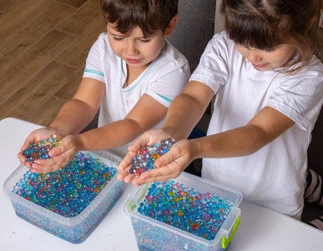 Children playing orbeez. Orbeez balls - sensory water beads.