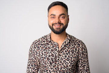 Face of happy young bearded Indian man smiling