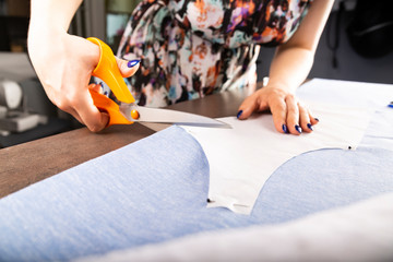 The seamstress cuts the material with sewing scissors