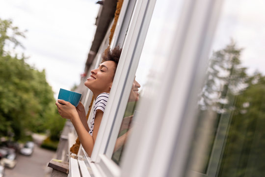 Woman looking out the window and drinking coffee