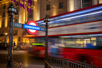 LONDON, UK - JUNE 17, 2013: Double Decker bus moves along the Regent Street at night near the Piccadilly Circus underground station entrance