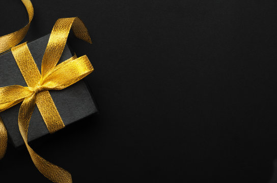 Holiday gift box with bow top view background. Birthday surprise, Christmas present and golden tape close up. Decorative backdrop with copyspace. Festive composition, surprise concept