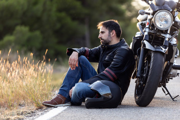 Young male sitting on the road, leaning on his motorcycle while waiting to the roadside assistance to repair the motorbike.
