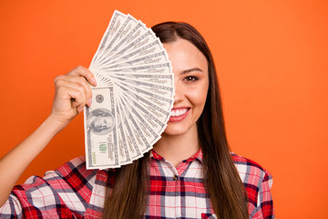 Closeup photo portrait of cheerful girl holding cash in hands closing face isolated over bright color background