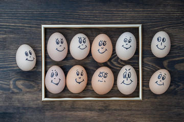 Picture golden frame and many funny eggs smiling on dark wooden wall background. Eggs family emotion face portrait. Concept funny food