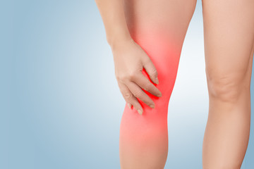 Female legs with the focus of the disease in the knee joint, the woman holds her hand on the sore spot, highlighted in red