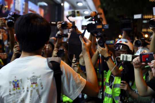 A man holds a mask as he talks to the media after he was questioned by the police at the Harbour city in Tsim Sha Tsui district, in Hong Kong