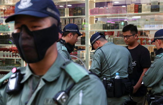 A man is questioned by the riot police near the police station in Tsim Sha Tsui district, in Hong Kong