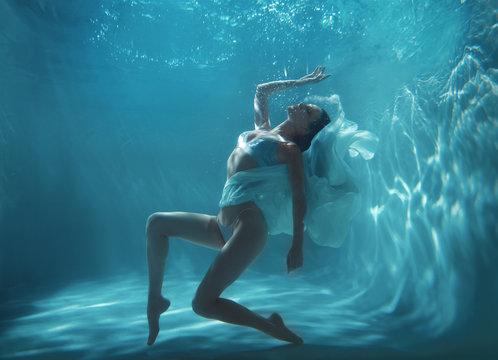 Fashion art photo of beautiful woman swimming and posing underwater