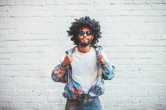 Stylish young man in a retro jacket. Fashion trends of 90s. Handsome hipster guy with beard with curly hair.