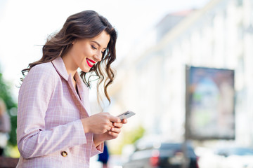 Fototapete - Close-up profile side view portrait of her she nice-looking attractive lovely charming pretty cheerful cheery wavy-haired girl using cell web service app 5g in downtown outdoors