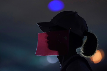 Woman is seen in silhouette with a piece of red cloth on her face outside the Mercedes-Benz Arena before the NBA exhibition game between Brooklyn Nets and Los Angeles Lakers in Shanghai