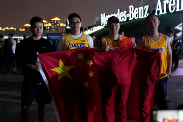 Fans in Los Angeles Lakers jerseys hold Chinese national flags as they pose for pictures outside the Mercedes-Benz Arena before the NBA exhibition game between Brooklyn Nets and Los Angeles Lakers in Shanghai