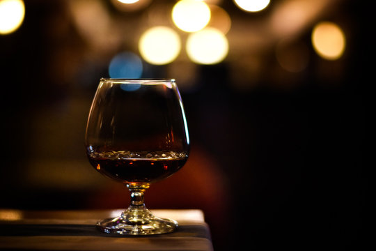 Whiskey in glass for adult on counter bar at to night.