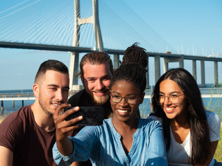 Happy friends taking group selfie while walking outside. Young men and women sitting on grass at river, using smart phone, smiling at screen. Photography concept