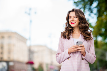 Fototapete - Portrait of her she nice-looking attractive charming glamorous lovely shine winsome cheerful dreamy wavy-haired lady holding in hands phone in park fresh air outdoors