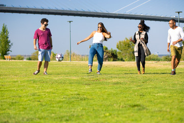 Multiethnic team of friends playing football in park. Young men and women kicking ball on grass. Weekend outdoors concept