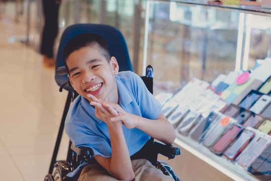Disabled child on wheelchair trying begged parents to buy a smartphone for him in IT shop , Special children's lifestyle, Life in the education age of special need kids, Happy disability kid concept.
