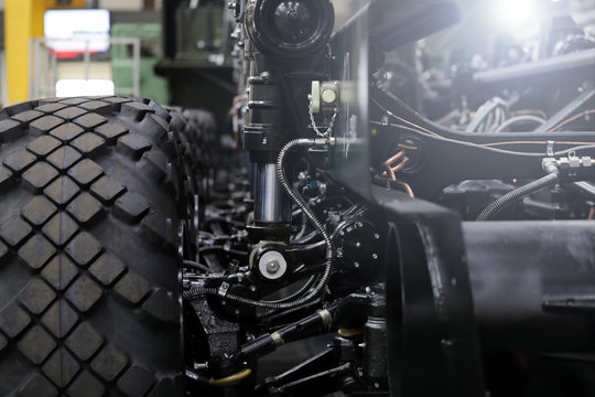 Close-up of new suspension system and shock absorber of car with wheel. Automotive part of atv off road. Mechanical engineering industry concept. Blurred background