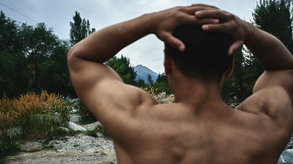 Kazakh muscular athlete man trains and exercises by the river in nature. Asian handsome does extreme fitness workout outdoors
